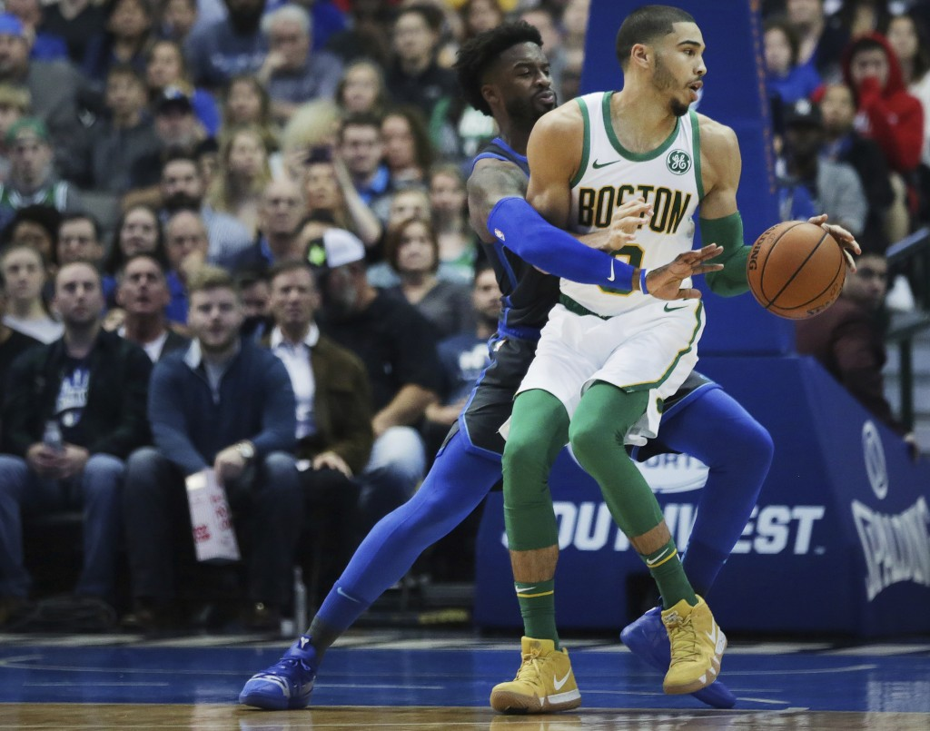Boston Celtics forward Jayson Tatum attempts to move the ball while defended by Dallas Mavericks guard Wesley Matthews in the first half of an NBA bas...