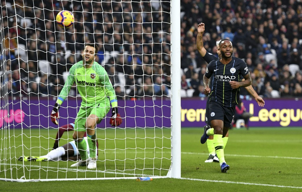 West Ham United goalkeeper Lukasz Fabianski, left, appears dejected as Manchester City's Raheem Sterling celebrates scoring his side's second goal of