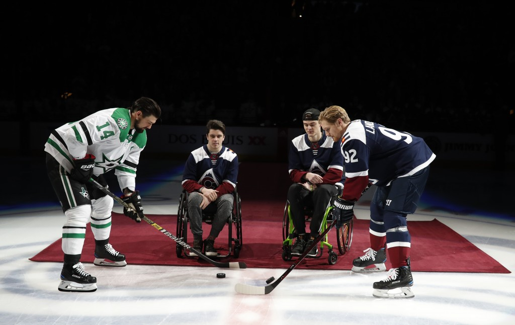 At left, Dallas Stars left wing Jamie Benn takes part in a ceremonial puck drop with Colorado Avalanche left wing Gabriel Landeskog, right, by two pla
