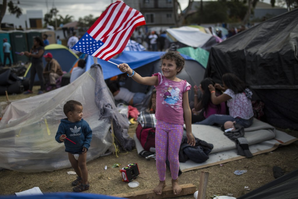 Seven-year-old Honduran migrant Genesis Belen Mejia Flores waves an American flag at U.S. border control helicopters flying overhead near the Benito J