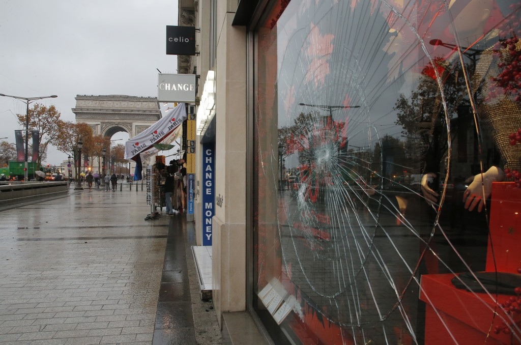 A smashed window of a shop is pictured at the Champs Elysees avenue in Paris, France, Sunday, Nov 25, 2018 in the aftermath of a protest against the r