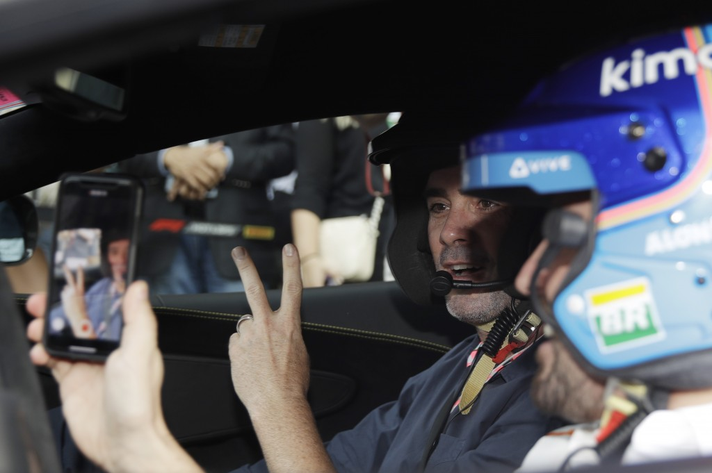 Mclaren driver Fernando Alonso of Spain, right, takes pictures of Nascar World champion Jimmie Johnson before driving a McLaren 570S car at the Yas Ma