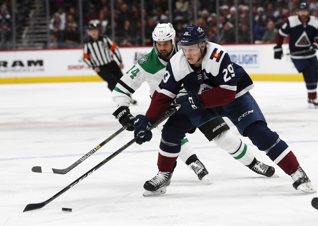 Colorado Avalanche center Nathan MacKinnon, front, drives downice past Dallas Stars left wing Jamie Benn in the first period of an NHL hockey game Sat