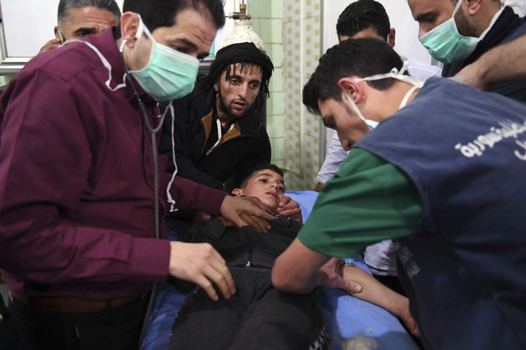 In this photo released by the Syrian official news agency SANA, shows medical staff treating a boy following a suspected chemical attack on his town o...
