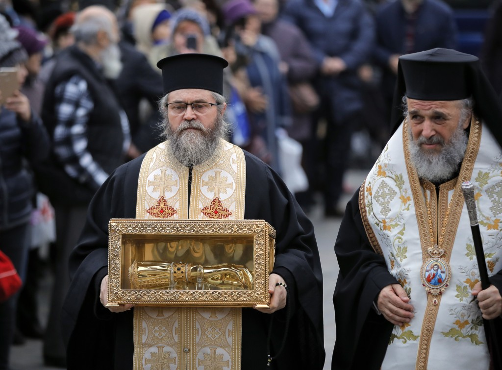 A priest holds the box containing the remains of Holy Hand of St. Andrew, in Bucharest, Romania, Saturday, Nov. 24, 2018, a day before the dedication ...