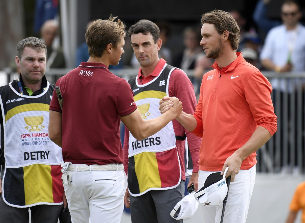 Belgium's Thomas Detry, left, and Thomas Pieters shake hands on the 18th green after winning the World Cup of Golf in Melbourne, Australia, Sunday, No...