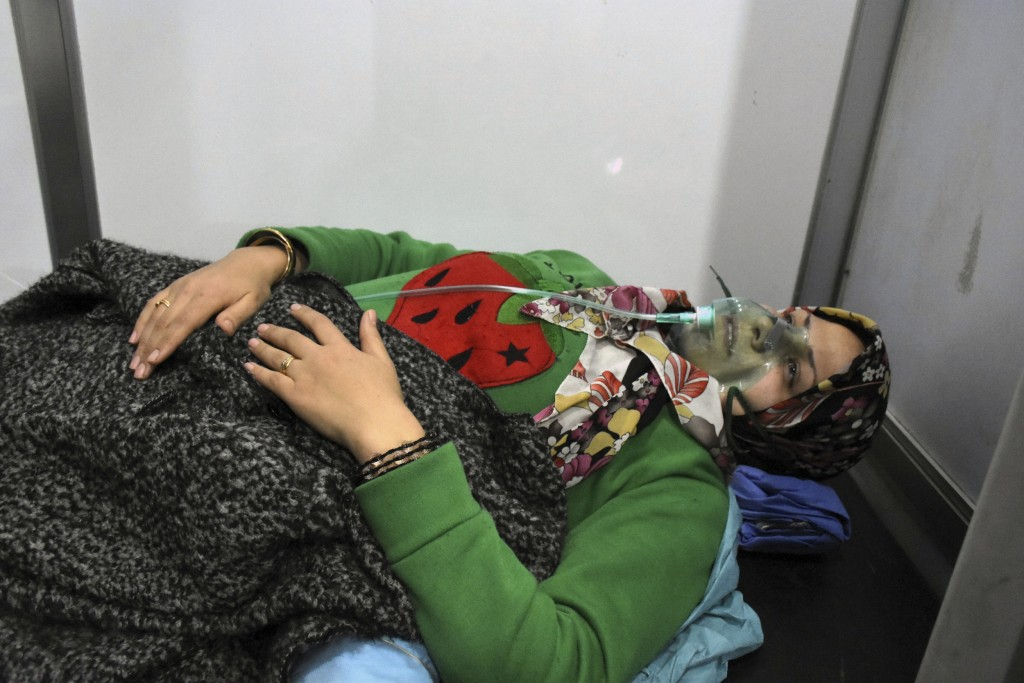 In this photo released by the Syrian official news agency SANA, shows a woman receiving oxygen through respirators following a suspected chemical atta