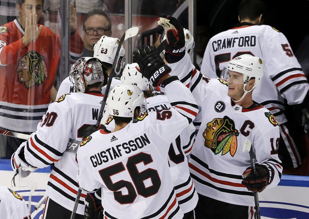Chicago Blackhawks defenseman Erik Gustafsson (56) is congratulated by center Jonathan Toews, right, after Gustafsson's overtime goal to defeat the Fl...