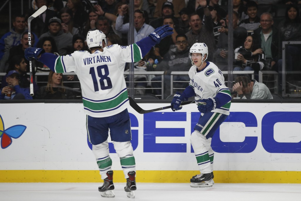 Vancouver Canucks' Elias Pettersson, right, of Sweden, celebrates his goal with Jake Virtanen during the third period of an NHL hockey game against th