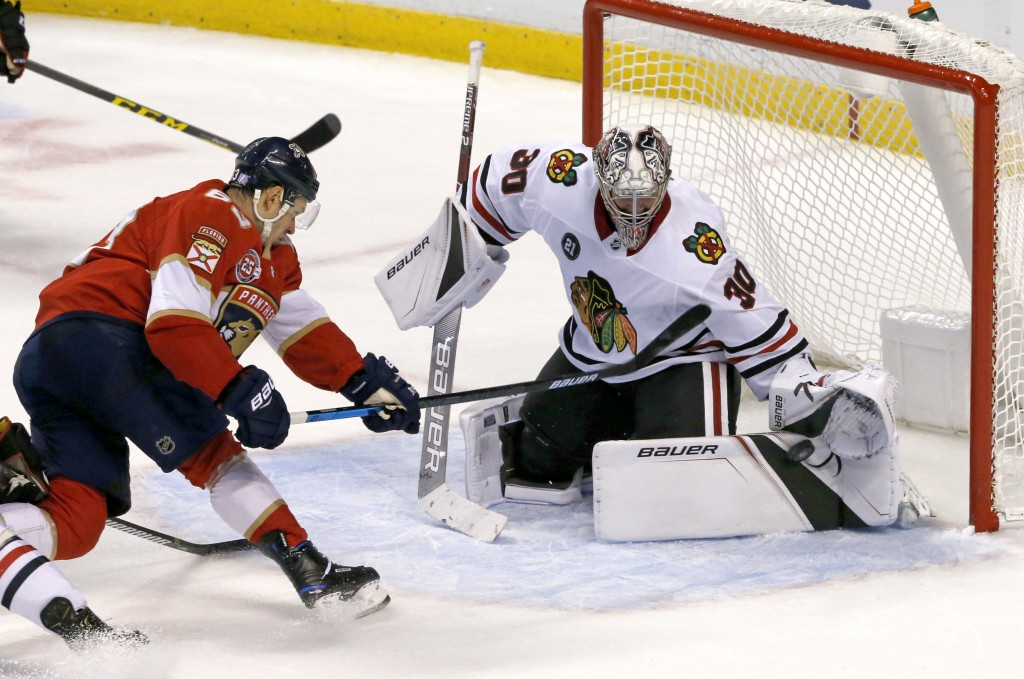 Chicago Blackhawks goaltender Cam Ward (30) deflects a shot by Florida Panthers right wing Evgenii Dadonov (63) in the second period of an NHL hockey ...