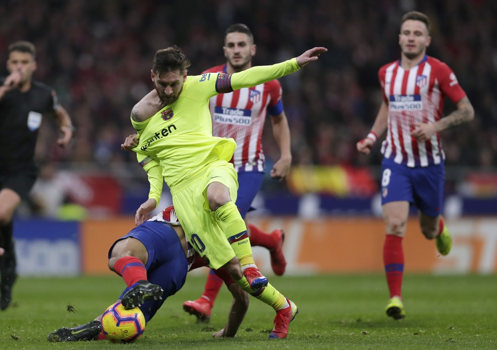 Barcelona's Lionel Messi, front right, duels for the ball with Athletico Madrid's Rodri during a Spanish La Liga soccer match between Atletico Madrid