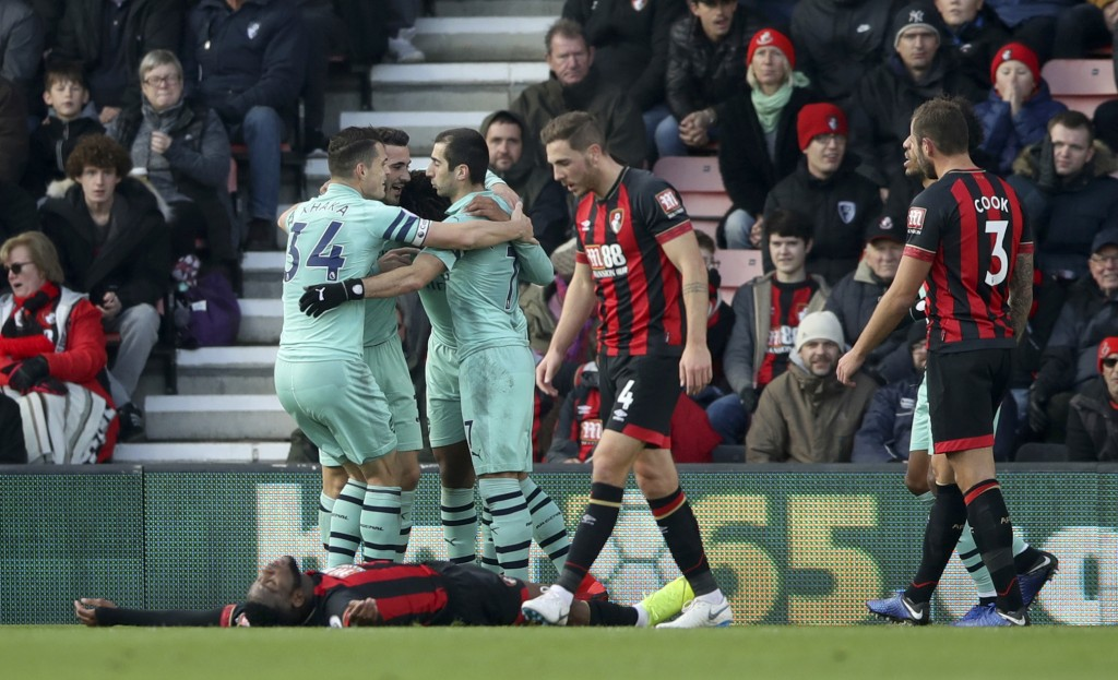Bournemouth's Jefferson Lerma lays on the ground dejected after conceding an own goal as Arsenal players celebrate, during a Premier League soccer mat...