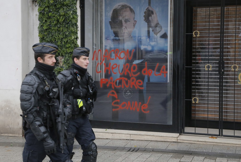 Police officers patrol at the Champs Elysees avenue in Paris, France, Sunday, Nov 25, 2018, in the aftermath of a protest against the rising of the fu...