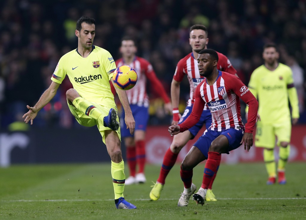 Barcelona's Sergio Busquets, left, duels for the ball with Athletico Madrid's Thomas Lemar during a Spanish La Liga soccer match between Atletico Madr
