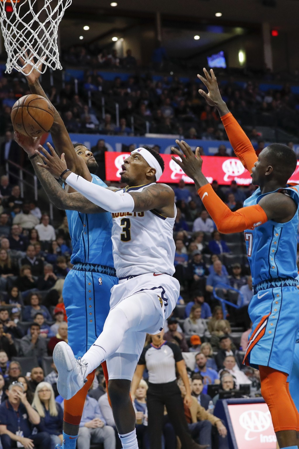 Denver Nuggets forward Torrey Craig (3) goes to the basket between Oklahoma City Thunder forward Paul George (13) and guard Dennis Schroder (17) durin...