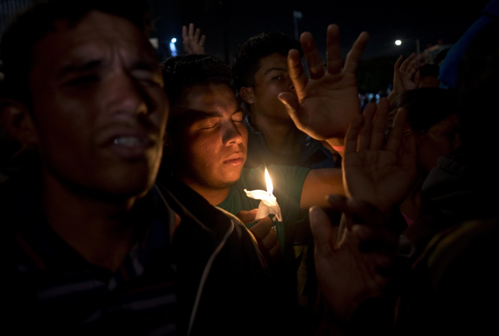 Migrants pray during a vigil outside the Benito Juarez Sports Center serving as a temporary shelter for Central American migrants in Tijuana, Mexico,