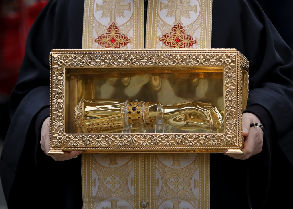 A priest holds the box containing the remains of Holy Hand of St. Andrew, in Bucharest, Romania, Saturday, Nov. 24, 2018, a day before the dedication