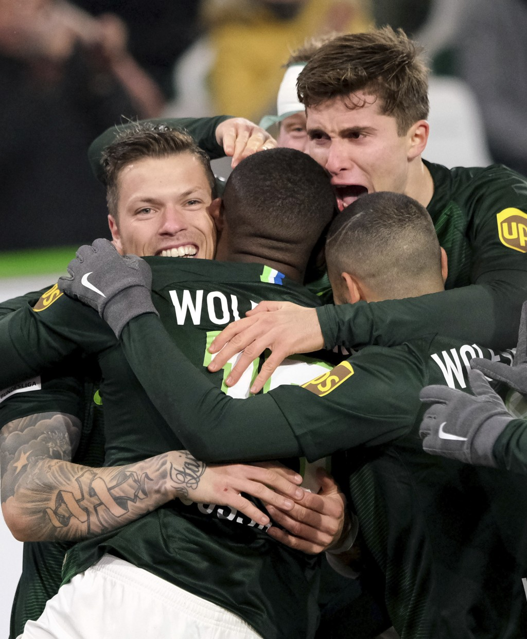 Wolfsburg's scorer Jerome Roussillon, center, and his teammates celebrate the opening goal   during the German Bundesliga soccer match between VfL Wol