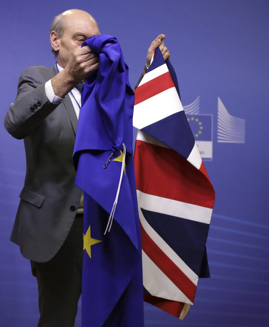 A member of protocol carries the Union Flag, right, and EU flag prior to the arrival of European Commission President Jean-Claude Juncker and British ...
