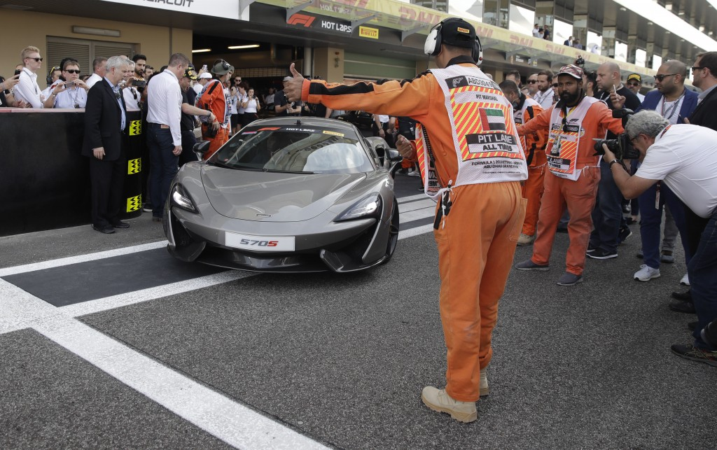 Mclaren driver Fernando Alonso of Spain, right, flanked by Nascar World champion Jimmie Johnson drive a McLaren 570S car at the Yas Marina racetrack i