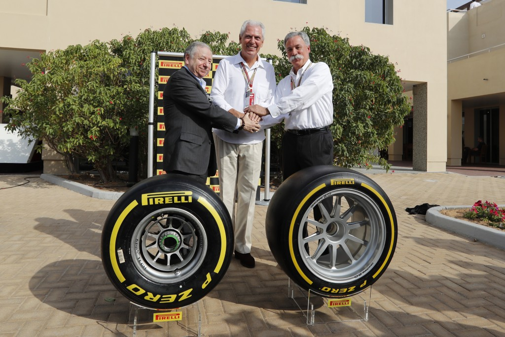 Formula One CEO Chase Carey, right, Pirelli CEO Marco Tronchetti Provera, left and FIA President Jean Todd pose for a picture behind the new Pirelli t...