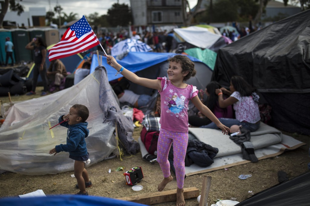 Seven-year-old Honduran migrant Genesis Belen Mejia Flores waves an American flag at U.S. border control helicopters flying overhead near the Benito J...