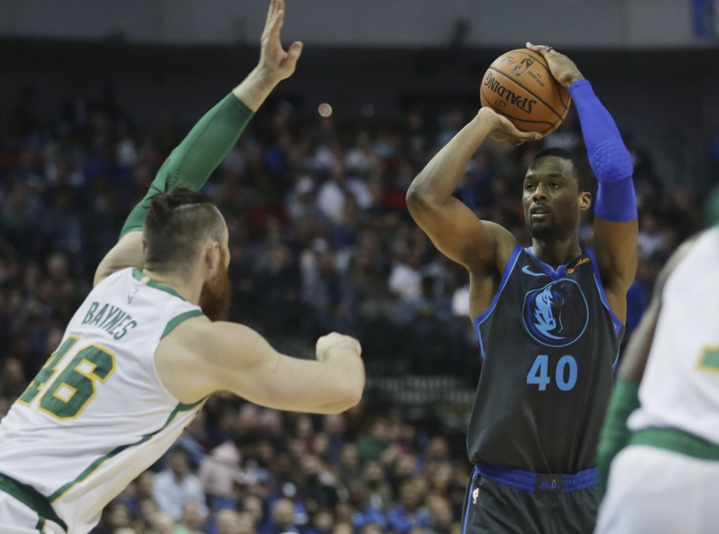 Dallas Mavericks forward Harrison Barnes, right, shoots while being defended by Boston Celtics center Aron Baynes in the first half of an NBA basketba