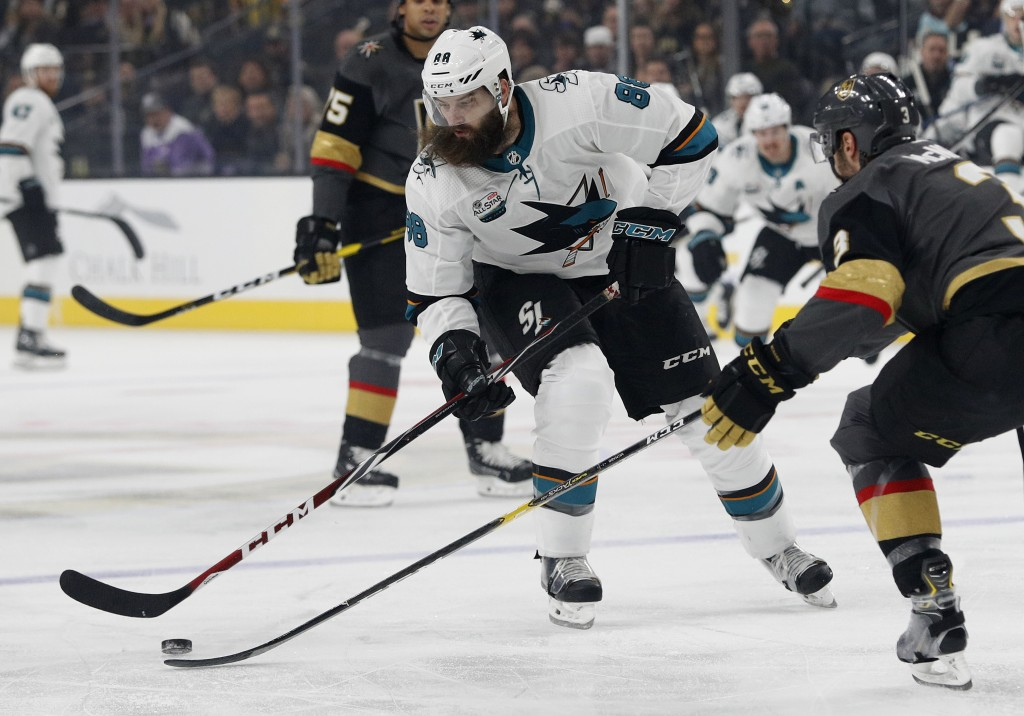 San Jose Sharks defenseman Brent Burns, left, tries to skate around Vegas Golden Knights defenseman Brayden McNabb during the first period of an NHL h...
