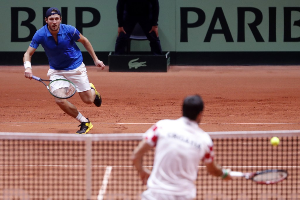 France's Lucas Pouille, left, run to return the ball from Croatia's Marin Cilic during the Davis Cup final between France and Croatia Sunday, Nov. 25,