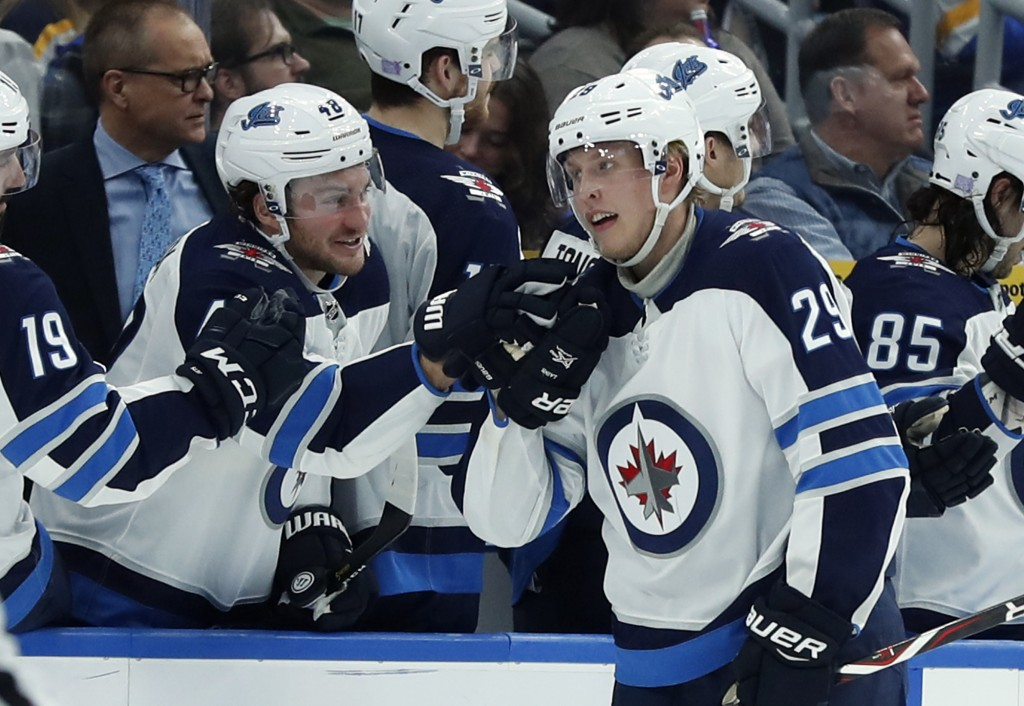 Winnipeg Jets' Patrik Laine (29), of Finland, is congratulated by Brendan Lemieux after scoring during the second period of an NHL hockey game against