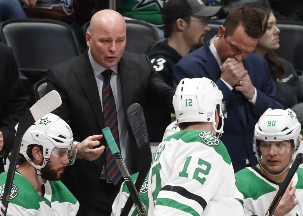 Dallas Stars head coach Jim Montgomery, back, confers with center Radek Faksa during a timeout in the second period of an NHL hockey game against the