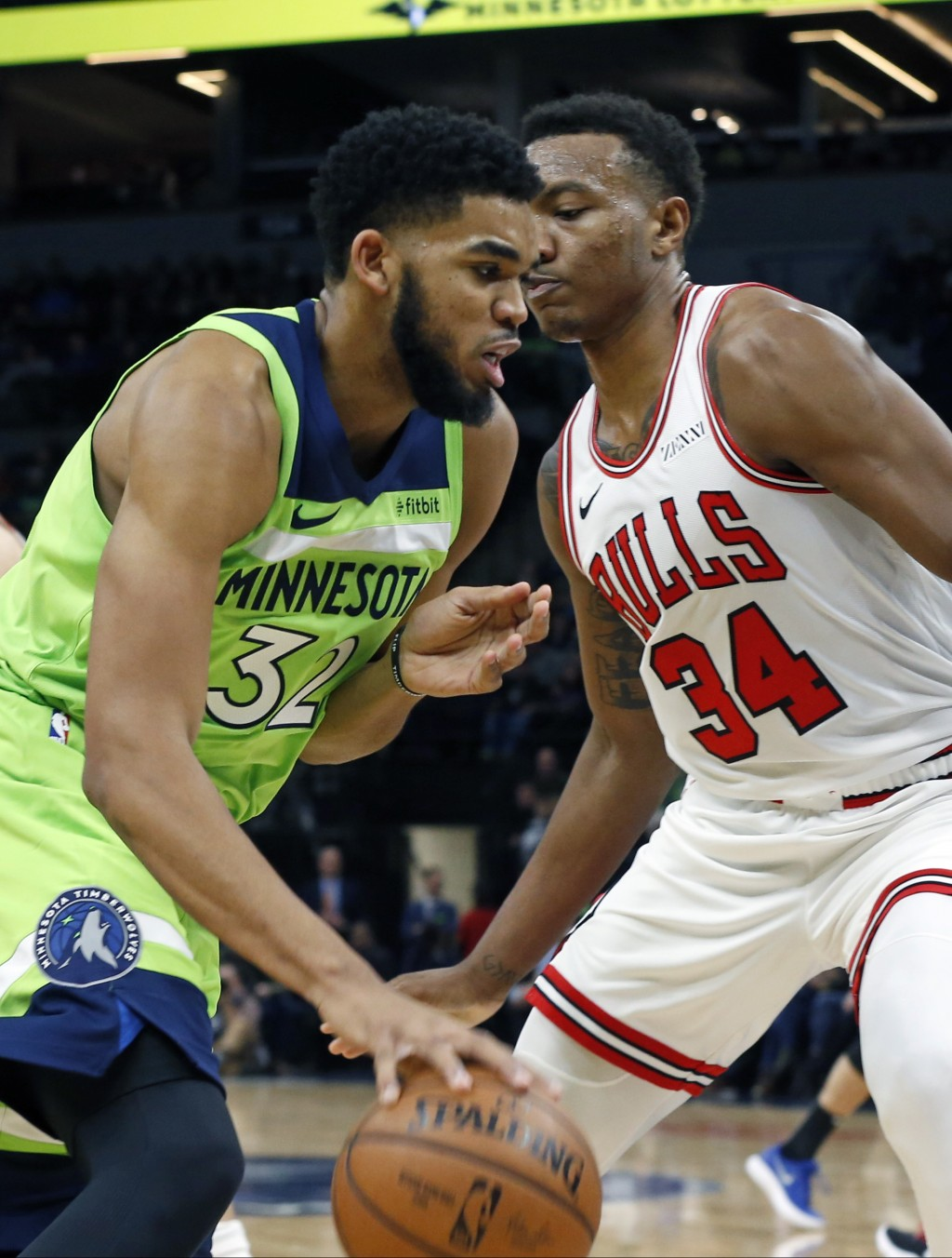 Minnesota Timberwolves' Karl-Anthony Towns, left, drives as Chicago Bulls' Wendell Carter Jr. defends in the first half of an NBA basketball game Satu...