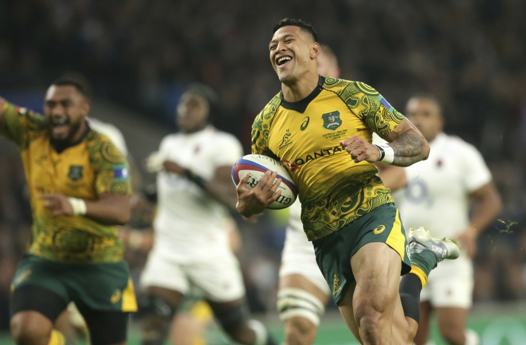 Australia's Israel Folau smiles as he crosses for a try during the rugby union international between England and Australia at Twickenham in London, Sa...