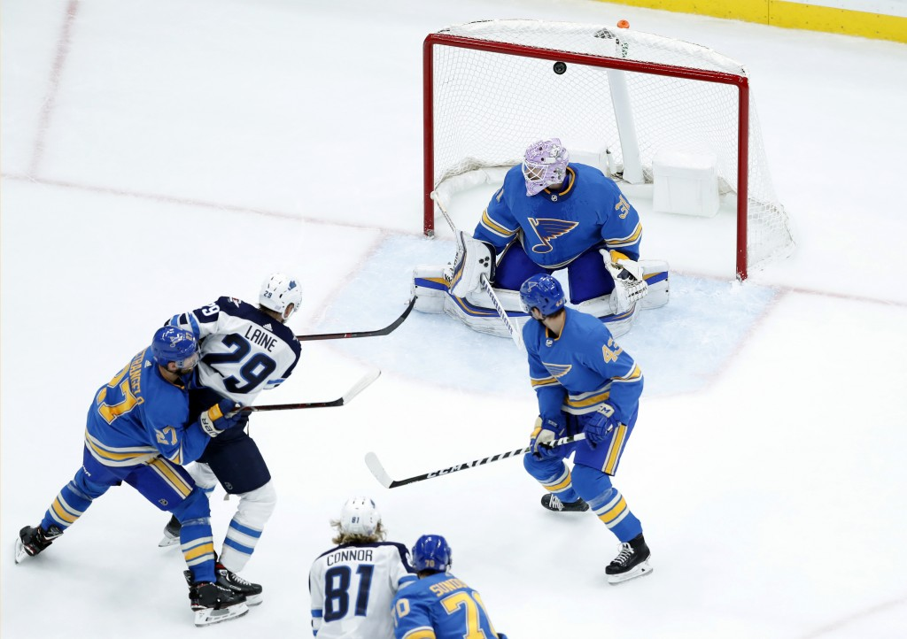 Winnipeg Jets' Patrik Laine (29), of Finland, scores past St. Louis Blues goaltender Chad Johnson (31) as Blues' Alex Pietrangelo (27) and Jordan Schm...