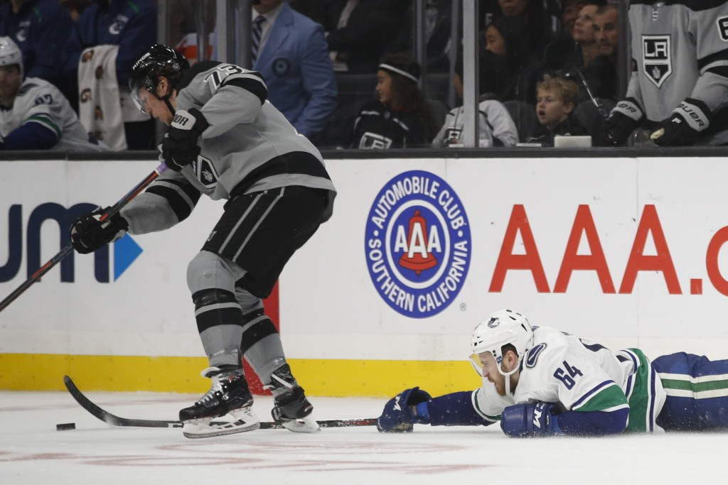 Vancouver Canucks' Tyler Motte, right, reaches for the puck against Los Angeles Kings' Tyler Toffoli during the second period of an NHL hockey game Sa