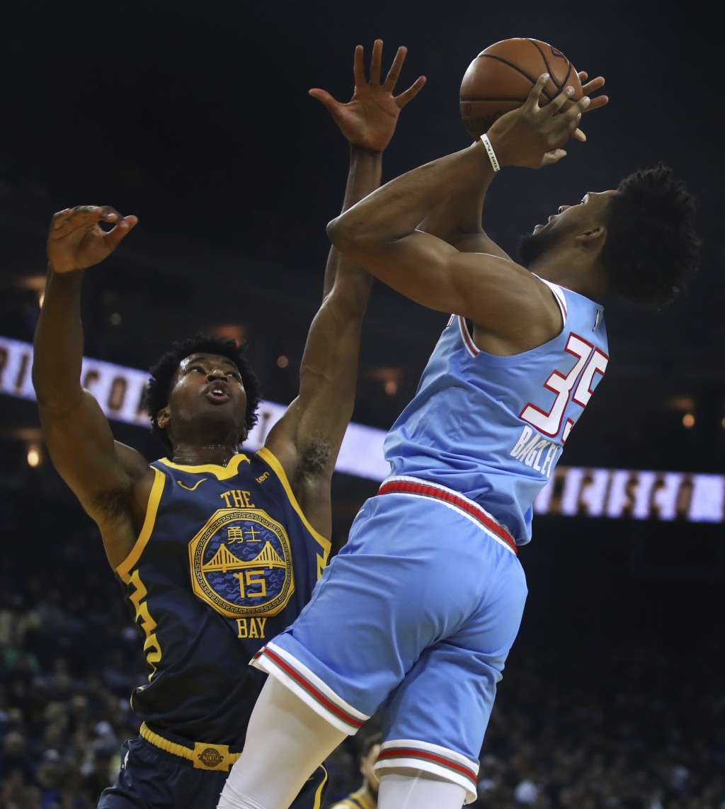 Sacramento Kings' Marvin Bagley III, right, shoots against Golden State Warriors' Damian Jones (15) during the first half of an NBA basketball game Sa...