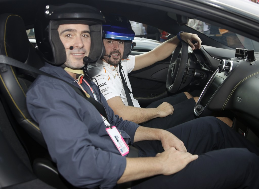Mclaren driver Fernando Alonso of Spain, right, is flanked by Nascar World champion Jimmie Johnson before driving a McLaren 570S car at the Yas Marina