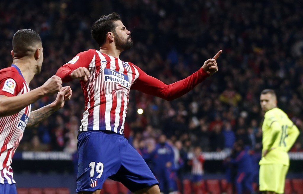 Atletico's Diego Costa, center, celebrates after scoring the opening goal during a Spanish La Liga soccer match between Atletico Madrid and FC Barcelo