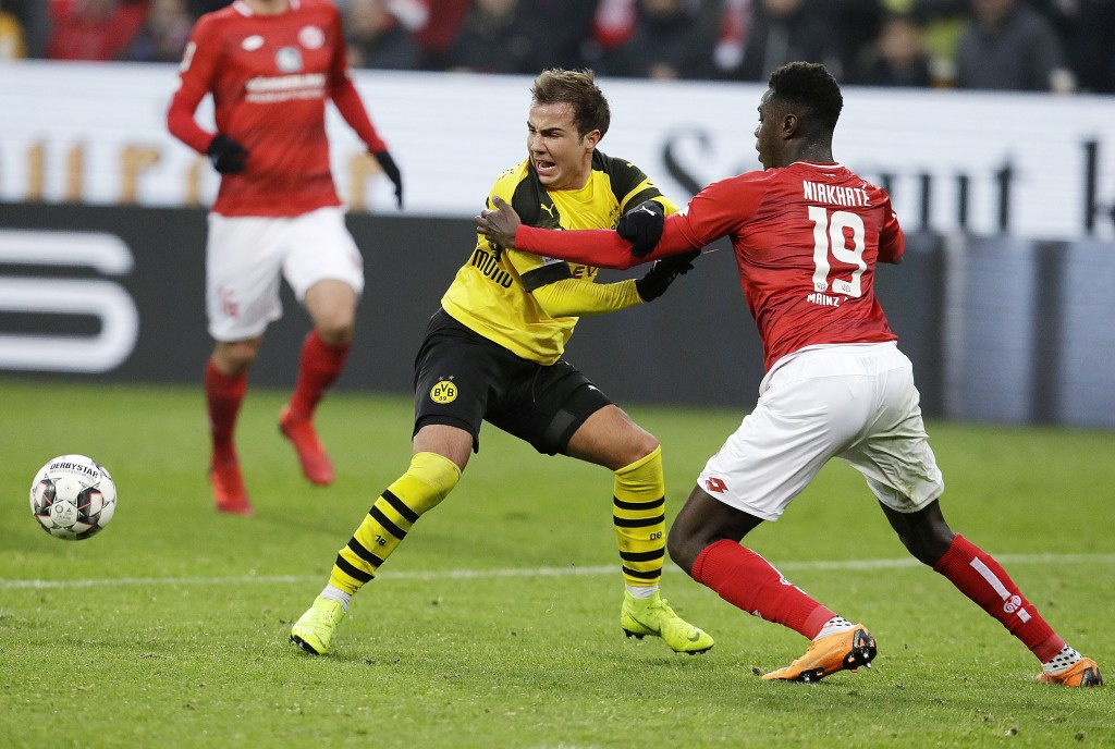 Mainz's Moussa Niakhate, right, and Dortmund's Mario Goetze, left, challenge for the ball during a German Bundesliga soccer match between FSV Mainz 05