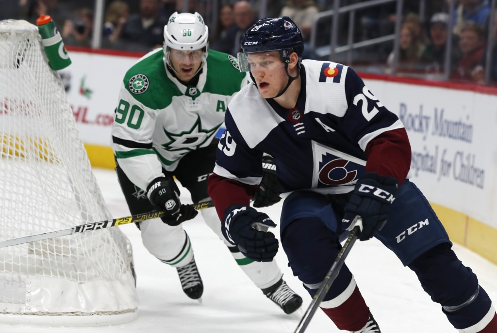 Colorado Avalanche center Nathan MacKinnon, right, tries to wrap around the net for a shot as Dallas Stars center Jason Spezza defends in the first pe