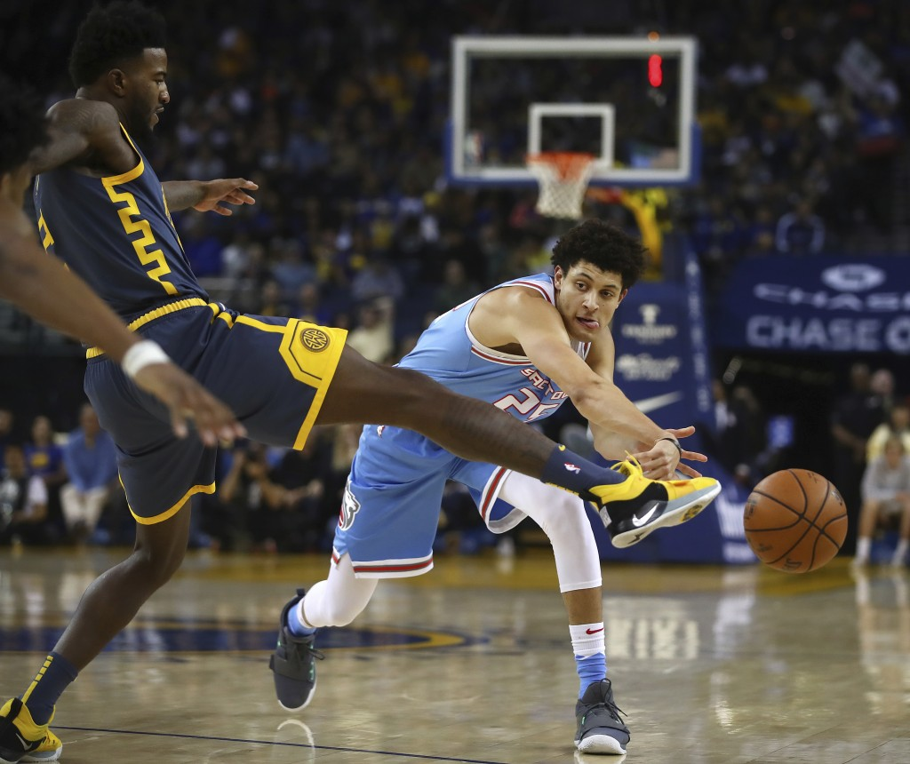 Sacramento Kings' Justin Jackson, right, passes the ball around Golden State Warriors' Jordan Bell during the first half of an NBA basketball game Sat...