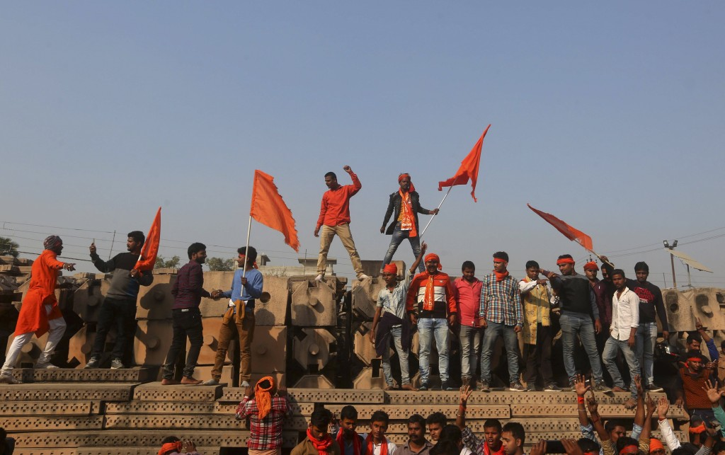 Supporters of Vishwa Hindu Parishad or World Hindu Council stand on blocks prepared for making a new temple as they gather for a rally to demand the c