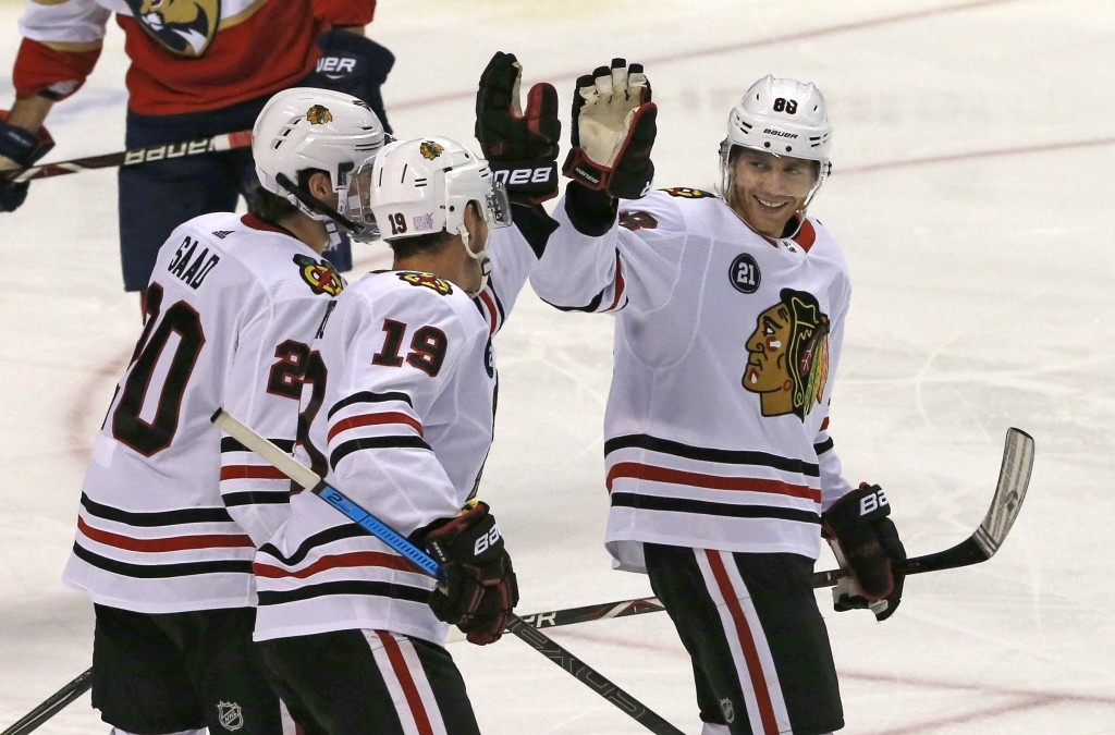 Chicago Blackhawks right wing Patrick Kane (88) celebrates his second period goal against the Florida Panthers with teammates Brandon Saad (20) and Jo...