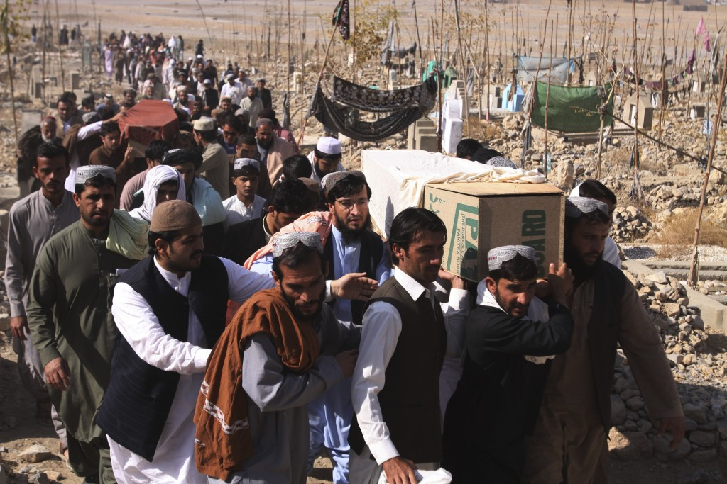 In this Saturday, Nov. 24, 2018 photo, people carry caskets of Pakistani civilians killed in a shootout during an attack on Chinese Consulate by milit