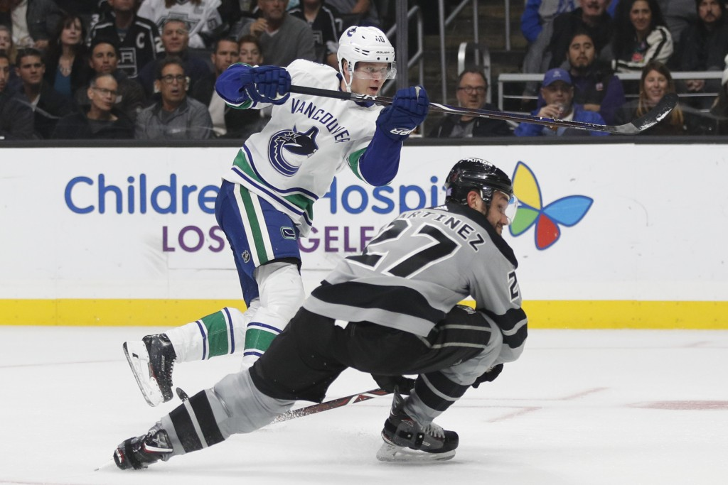 Vancouver Canucks' Elias Pettersson, top, of Sweden, and Los Angeles Kings' Alec Martinez watch the puck hit by Pettersson enter the net for a goal du