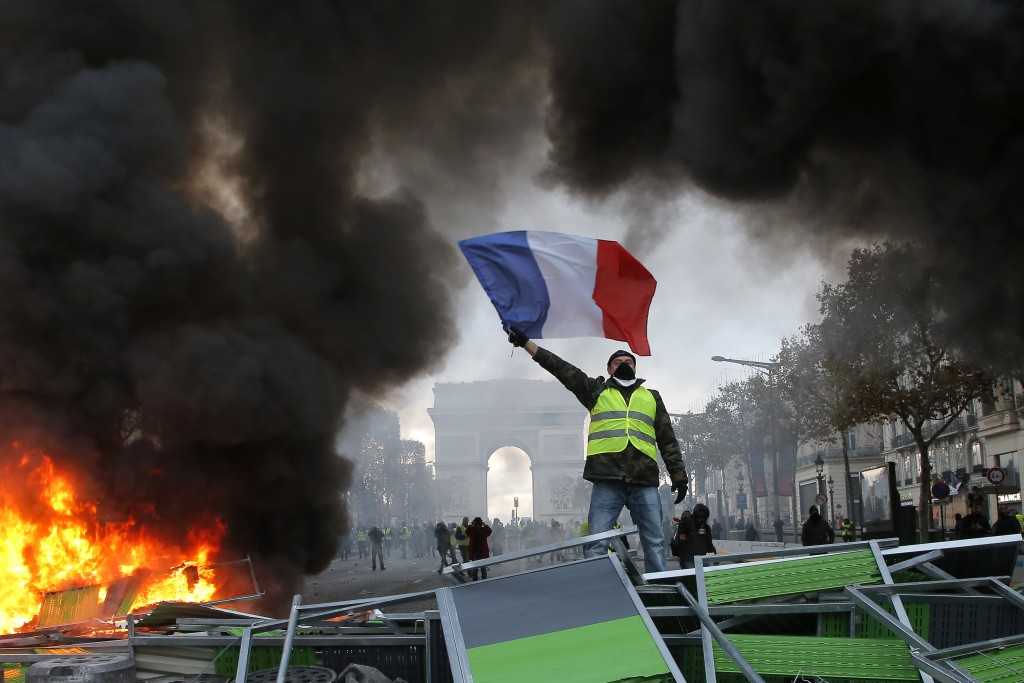 A demonstrator waves the French flag onto a burning barricade on the Champs-Elysees avenue with the Arc de Triomphe in background, during a demonstrat