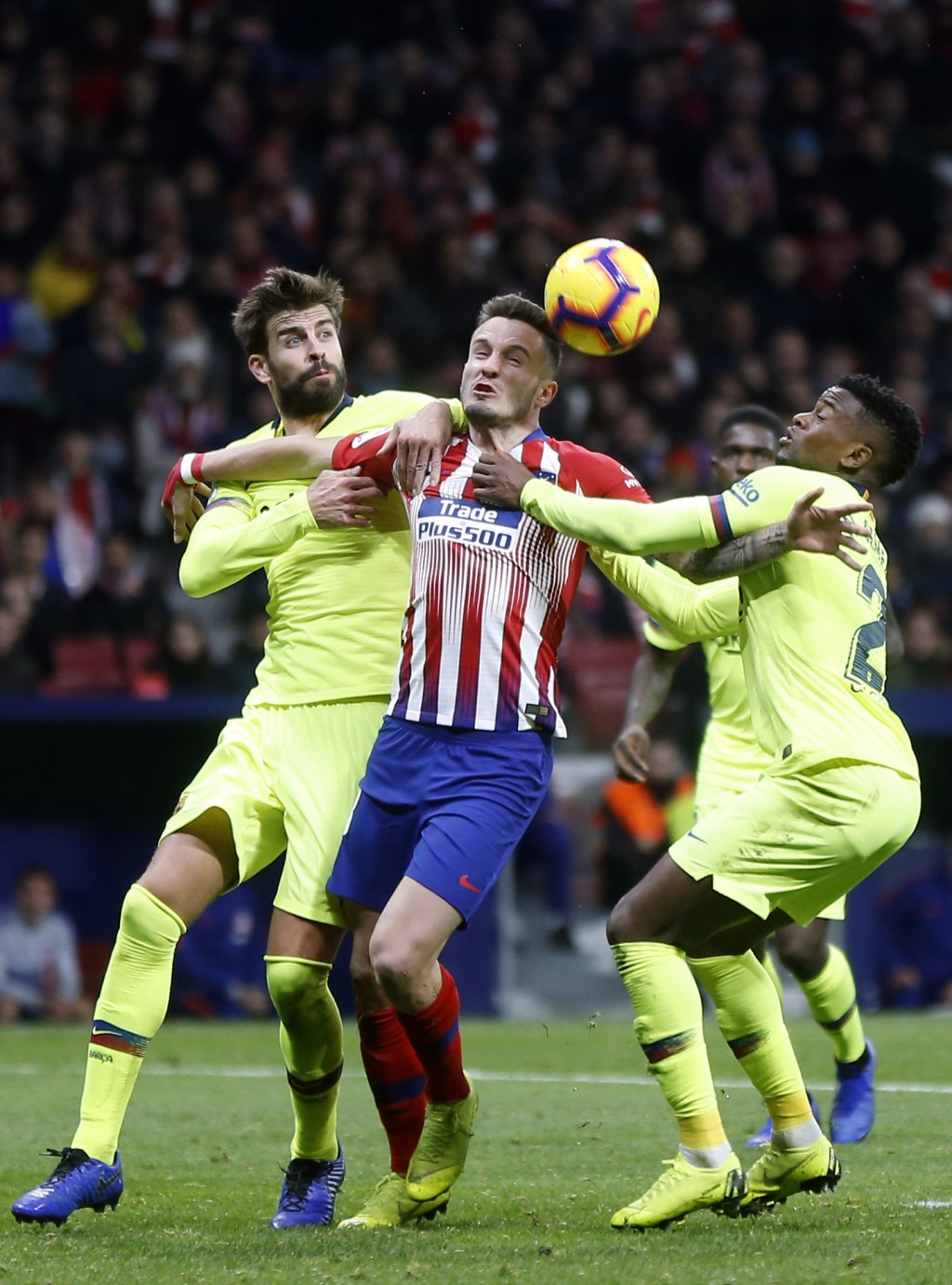 Atletico's Saul Niguez fights for the ball with Barcelona's Gerard Pique and Nelson Semedo, right, during a Spanish La Liga soccer match between Atlet...