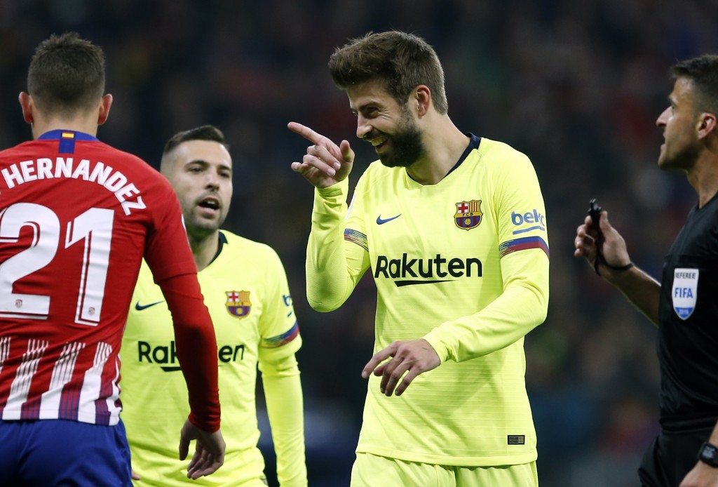 Barcelona's Gerard Pique, center, gestures during a Spanish La Liga soccer match between Atletico Madrid and FC Barcelona at the Metropolitano stadium...