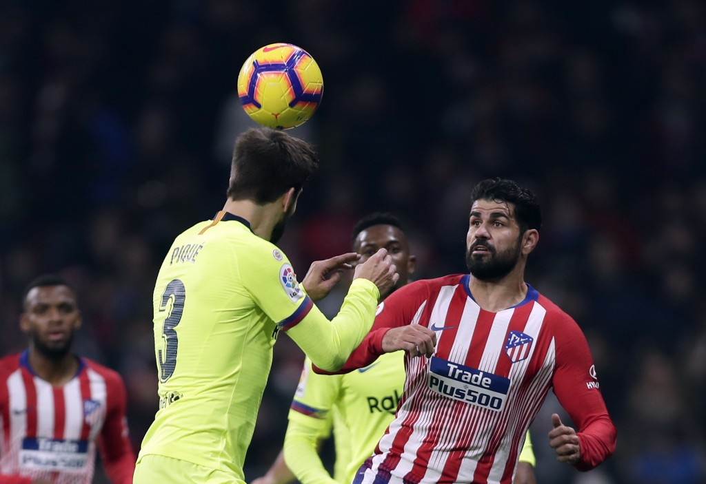 Athletico Madrid's Diego Costa, right, duels for the ball with Barcelona's Gerard Pique during a Spanish La Liga soccer match between Atletico Madrid