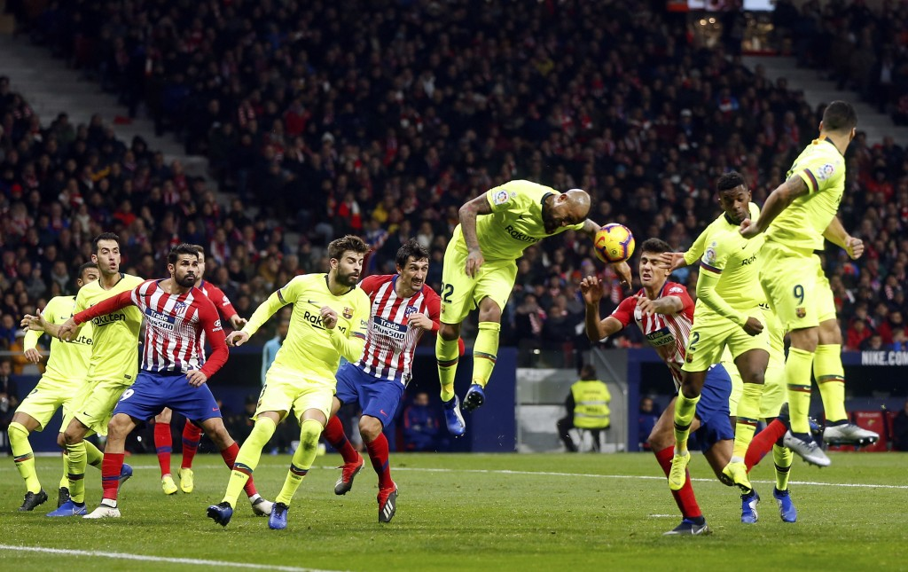 Barcelona's Arturo Vidal center jumps for the ball leaving his arm in the way during a Spanish La Liga soccer match between Atletico Madrid and FC Bar...
